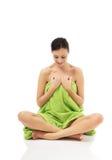 Vrouwenzitting in handdoek met de benen over elkaar wordt verpakt die Stock Afbeeldingen