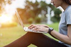Vrouwenzitting in het park bij zonsondergang tijd en het gebruiken van laptop comput stock afbeeldingen