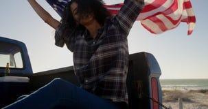 Vrouwenzitting met golvende Amerikaanse vlag op een ver*beteren vrachtwagen 4k stock video