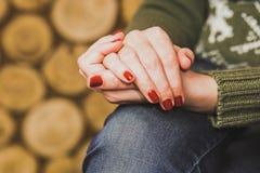 Vrouwenzitting met haar die handen op knie worden gekruist Royalty-vrije Stock Afbeelding