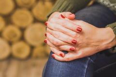 Vrouwenzitting met haar die handen op knie worden gekruist Stock Foto