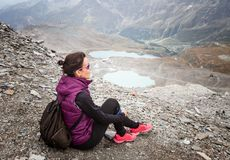 Vrouwenzitting met haar rugzak die het landschap bekijken royalty-vrije stock fotografie