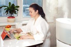 Vrouwenzitting met tabletpc op de achtergrond van luchtbevochtiger Royalty-vrije Stock Foto's
