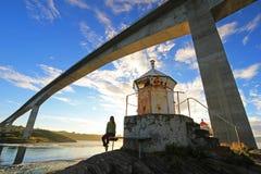 Vrouwenzitting onder de brug bij de fjord van de draaikolken van de maalstroom van Saltstraumen, Nordland, Noorwegen royalty-vrije stock foto's