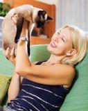 Vrouwenzitting op bank met haar kat Royalty-vrije Stock Afbeelding