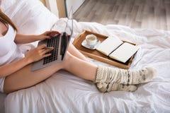 Vrouwenzitting op Bed die aan Laptop werken stock afbeelding