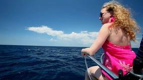 Vrouwenzitting op boog van varende boot die van mening van overzees genieten stock video
