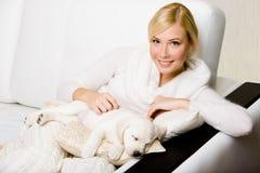 Vrouwenzitting op de bank met slaappuppy van Labrador stock afbeelding
