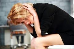 Vrouwenzitting op de bureaustoel wat betreft haar hoofd royalty-vrije stock afbeelding