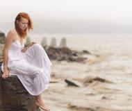 Vrouwenzitting op de kust op strand Stock Foto