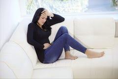 Vrouwenzitting op de laag thuis met maagpijn Stock Afbeeldingen