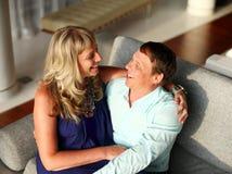 Vrouwenzitting op de overlapping van de mens en zij allebei glimlachen royalty-vrije stock fotografie