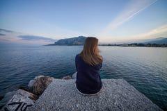 Vrouwenzitting op de rand van pijler die kalm overzees landschap bewonderen stock foto's