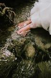 Vrouwenzitting op de rots in een rivier, voeten dichtbij de waterspiegel royalty-vrije stock foto