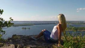 Vrouwenzitting op de rotsachtige Bank van de Volga rivier Slowmotion stock footage