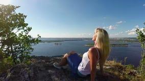 Vrouwenzitting op de rotsachtige Bank van de Volga rivier Slowmotion stock videobeelden