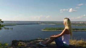 Vrouwenzitting op de rotsachtige Bank van de Volga rivier Slowmotion stock video