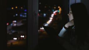 Vrouwenzitting op de vensterbank in de donkere nacht en het bekijken straat Het gebruiken van tablet voor Web stock videobeelden