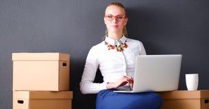 Vrouwenzitting op de vloer dichtbij dozen met laptop Stock Fotografie