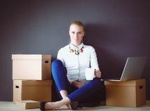 Vrouwenzitting op de vloer dichtbij dozen met laptop Onderneemster Stock Foto