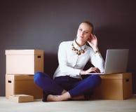 Vrouwenzitting op de vloer dichtbij dozen met laptop Onderneemster Stock Afbeeldingen