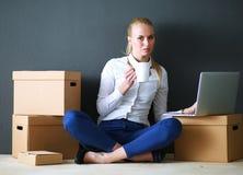 Vrouwenzitting op de vloer dichtbij dozen met laptop Onderneemster Royalty-vrije Stock Afbeelding