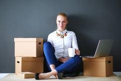 Vrouwenzitting op de vloer dichtbij dozen met laptop Onderneemster Royalty-vrije Stock Fotografie