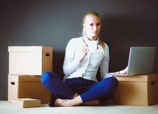 Vrouwenzitting op de vloer dichtbij dozen met laptop Onderneemster Stock Fotografie