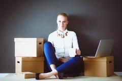 Vrouwenzitting op de vloer dichtbij dozen met laptop Onderneemster Stock Foto's