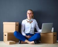 Vrouwenzitting op de vloer dichtbij dozen met laptop Onderneemster Royalty-vrije Stock Foto's