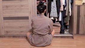 Vrouwenzitting op de vloer dichtbij garderobe en het kiezen van kleren stock footage