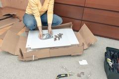 Vrouwenzitting op de vloer thuis en het assembleren meubilair die handhulpmiddelen met behulp van stock fotografie