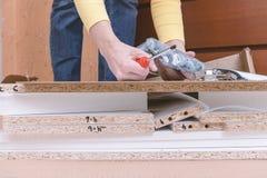 Vrouwenzitting op de vloer thuis en het assembleren meubilair die handhulpmiddelen met behulp van royalty-vrije stock foto's
