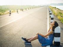 Vrouwenzitting op de weg Royalty-vrije Stock Foto