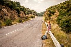 Vrouwenzitting op de wegomheining Royalty-vrije Stock Fotografie