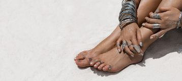 Vrouwenzitting op de de zandhanden en voeten met etnische accessori Royalty-vrije Stock Afbeeldingen