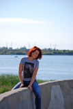 Vrouwenzitting op dijk door rivier Royalty-vrije Stock Fotografie