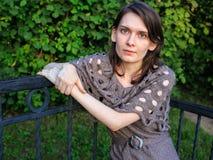 Vrouwenzitting op een bank in de groene tuin of het park Stock Foto's