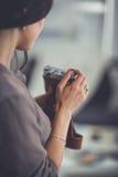 Vrouwenzitting op een bank in haar huis met camera Stock Foto