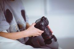 Vrouwenzitting op een bank in haar huis met camera Stock Fotografie