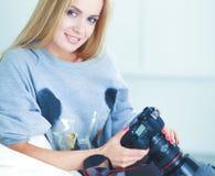 Vrouwenzitting op een bank in haar huis met camera Royalty-vrije Stock Foto's