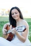 Vrouwenzitting op een gebloeide weide het spelen gitaar stock foto