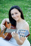 Vrouwenzitting op een gebloeide weide het spelen gitaar royalty-vrije stock foto