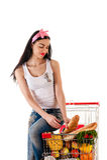 Vrouwenzitting op een het winkelen karretje Stock Fotografie