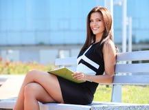 Vrouwenzitting op een houten bank in een park stock foto's