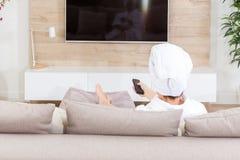 Vrouwenzitting op een laag met handdoek op haar hoofd het letten op TV stock foto's