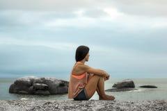Vrouwenzitting op een rots bij zonsondergang op Bakovern-Strand, Cape Town royalty-vrije stock foto's
