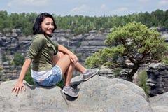 Vrouwenzitting op een rotsvooruitzicht stock afbeelding