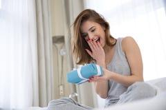 Vrouwenzitting op het bed met gift stock fotografie