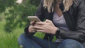 Vrouwenzitting op het gras met een telefoon in haar handen en een slim horloge voorraad Het concept technologieën binnen elke dag stock videobeelden